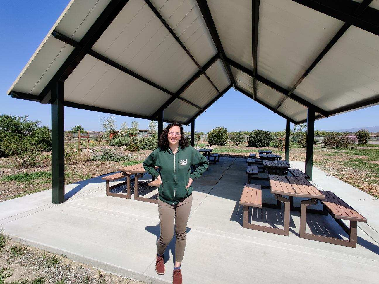 Our City Forest employee in green sweatshirt smiling and standing in front of outdoor pavilion with picnic tables