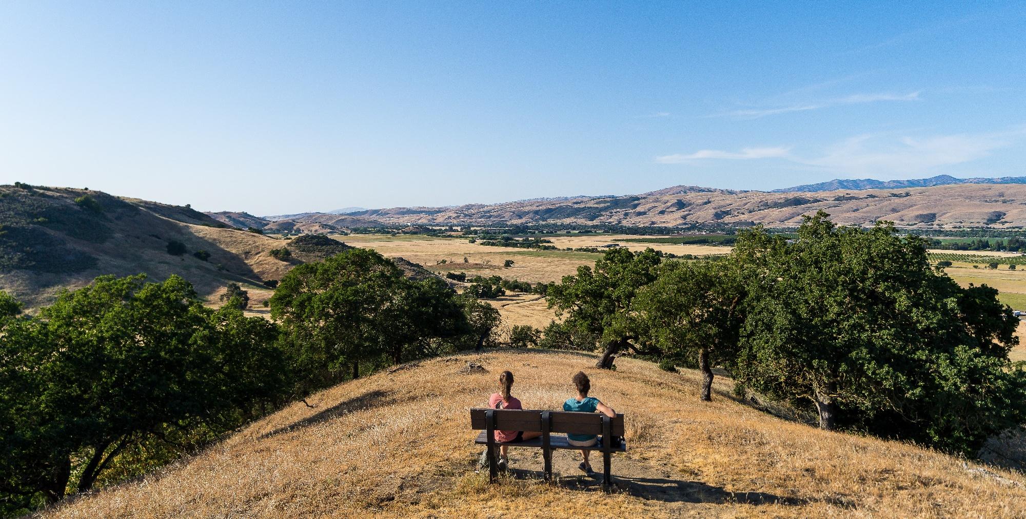 Two hikers on bench overlooking Coyote Valley below